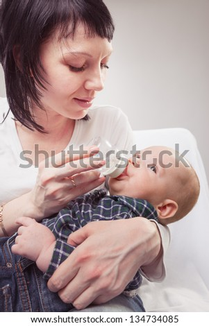 Happy mother gives to drink to the baby water from a small bottle