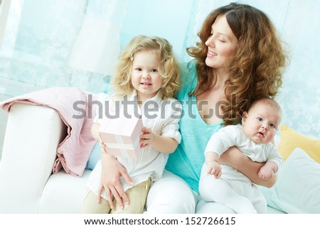 Happy mother giving her children a hug, her daughter holding a gift-box - stock photo