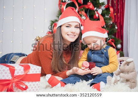 Happy mother giving to baby Christmas gift, candle. Gift box. Decorated christmas tree. New Year. Looking at camera