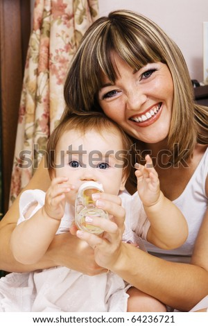 Happy mother giving to drink to her cute little daughter - stock photo