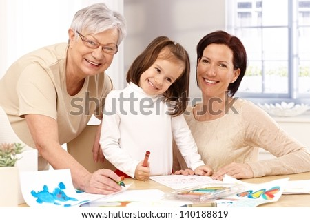 Happy mother, granny and little daughter playing together, drawing at table. - stock photo