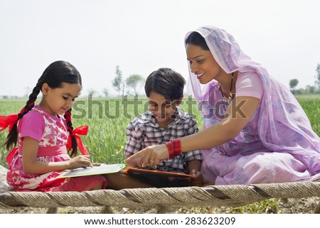 Happy mother guiding children with their homework - stock photo