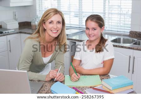 Happy mother helping daughter doing homework - stock photo