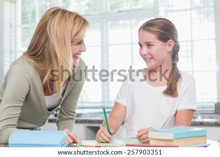 Happy mother helping daughter doing homework at home in the kitchen