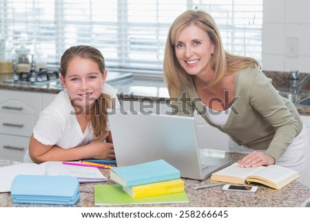 Happy mother helping daughter doing homework at home in the kitchen - stock photo