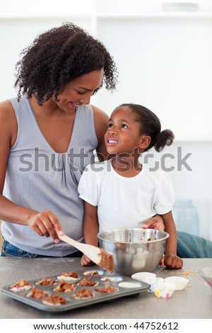 Happy mother helping her daughter cooking biscuits in the kitchen - stock photo