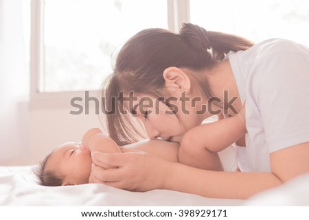 Happy mother holding adorable child baby boy soft color