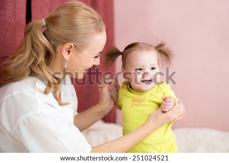 Happy mother holding baby hands at home - stock photo