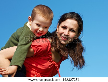 Happy mother holding cheerful child on her back over blue sky - stock photo