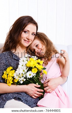 Happy mother holding flowers and embracing lovely daughter - stock photo