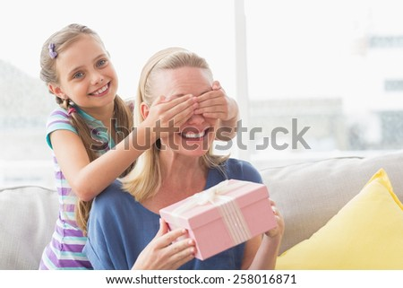 Happy mother holding gift with daughter covering her eyes at home in living room - stock photo