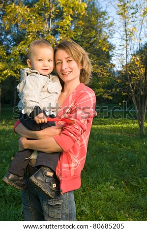 Happy mother holding her baby boy in the autumn park