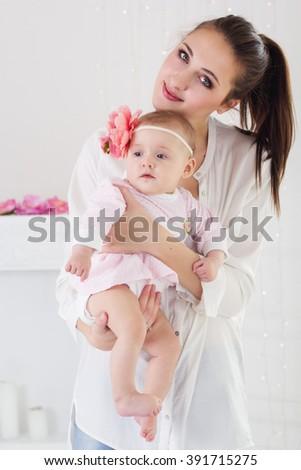 Happy mother holding her baby girl in studio - stock photo