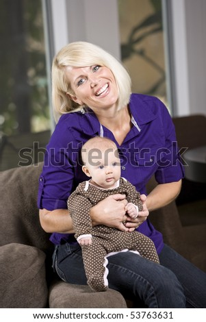 Happy mother holding 3 month old baby on couch at home