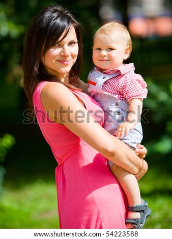 Happy mother holding one year son summer outdoors