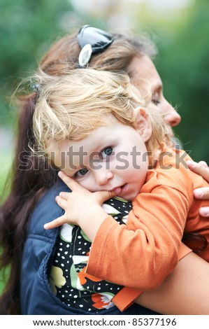 Happy mother holding the child in her hands outdoors