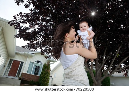 Happy mother holding up her adorable daughter - stock photo