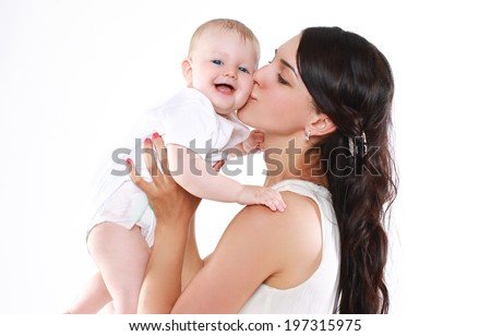 Happy mother holds and kissing her baby - stock photo