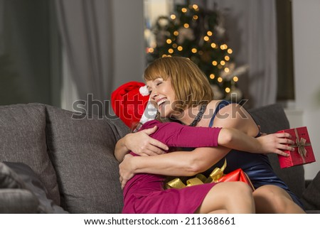 Happy mother hugging girl during Christmas at home - stock photo