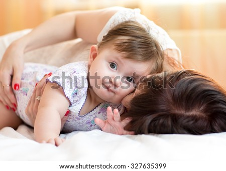 happy mother hugging her baby daughter lying on bed - stock photo