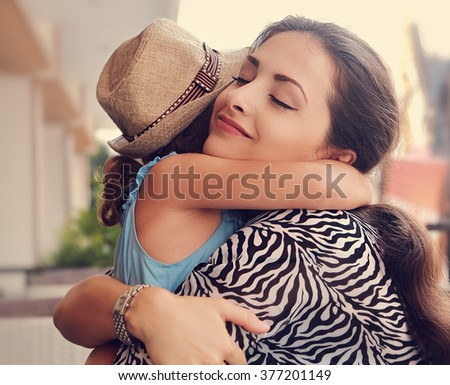Happy mother hugging her daughter with love and natural emotion with closed eyes. Closeup toned portrait of family love - stock photo