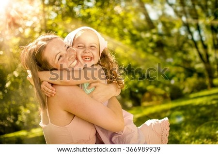 Happy mother hugging with her child in nature on sunny day - photo with flare