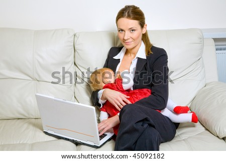 happy mother in business suit with laptop breastfeeding her baby - stock photo