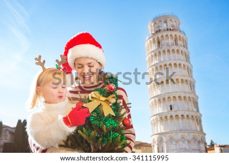 Happy mother in Christmas hat and daughter wearing funny reindeer antlers holding Christmas tree in front of Leaning Tour of Pisa, Italy. They spending exciting Christmas time traveling. - stock photo