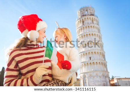 Happy mother in Christmas hat and daughter wearing funny reindeer antlers holding Italian flag in front of Leaning Tour of Pisa, Italy. They spending exciting Christmas time traveling. - stock photo