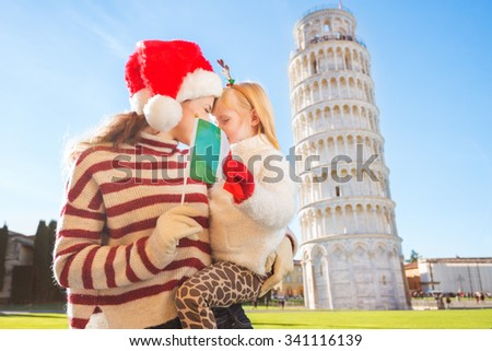 Happy mother in Christmas hat and daughter wearing funny reindeer antlers hugging behind Italian flag in front of Leaning Tour of Pisa, Italy. They spending exciting Christmas time traveling. - stock photo