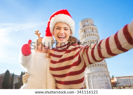 Happy mother in Christmas hat taking selfie with daughter wearing funny reindeer antlers and showing thumbs up in front of Leaning Tour of Pisa, Italy. They spending exciting Christmas time traveling - stock photo
