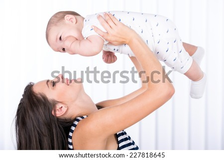 Happy mother is holding her baby boy, isolated on white. - stock photo