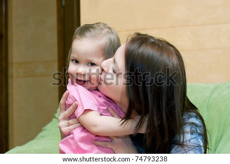 happy mother is kissing small daughter
