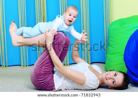 Happy mother is playing with her baby. - stock photo