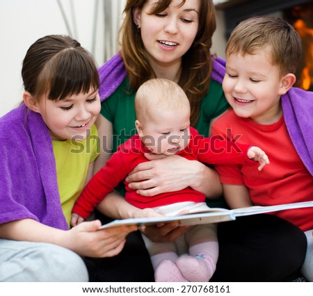 Happy mother is reading book with children - stock photo
