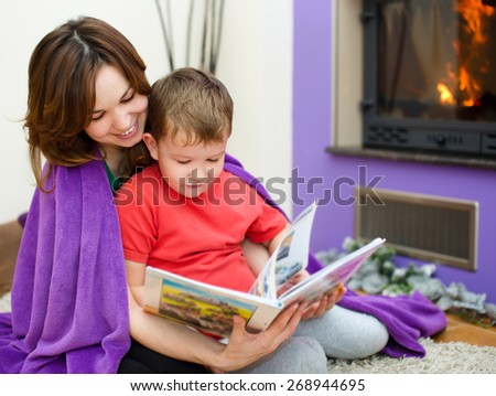Happy mother is reading book with her son - stock photo
