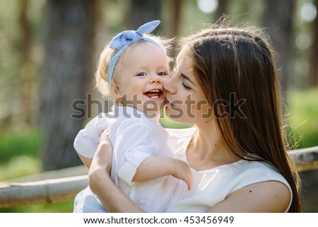 happy mother kiss her baby daughter smiling in the green park near forest in sunlight outdoor shot - stock photo