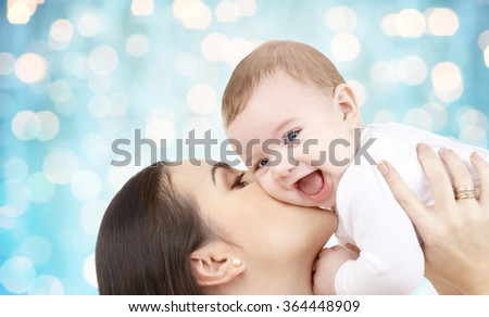 happy mother kissing her baby over blue lights - stock photo
