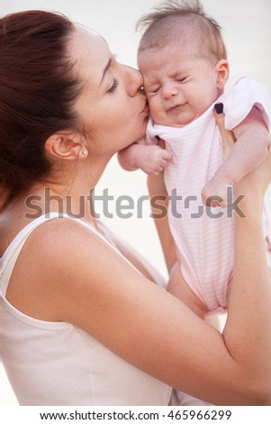 Happy mother kissing her cute baby. Motherhood and children concept