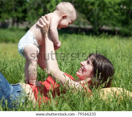 Happy mother lay with new born baby on grass in park - stock photo