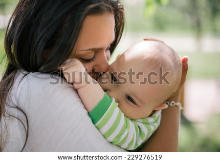Happy mother lay with newborn baby - stock photo