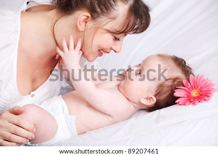 Happy mother looking at baby in bed