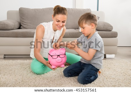 Happy Mother Looking At Boy Inserting Coin In Piggybank - stock photo