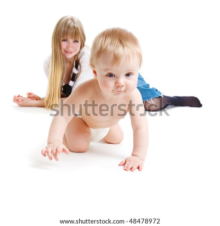 Happy mother looking at her crawling  baby son - stock photo