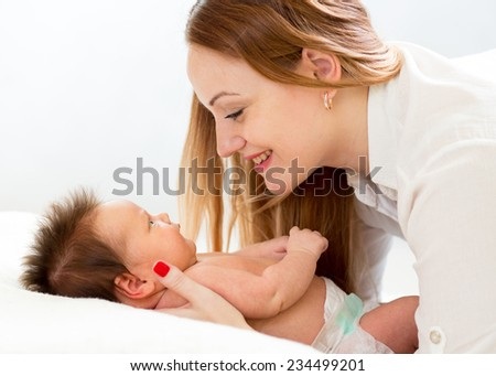 Happy mother looking at her newborn baby - stock photo