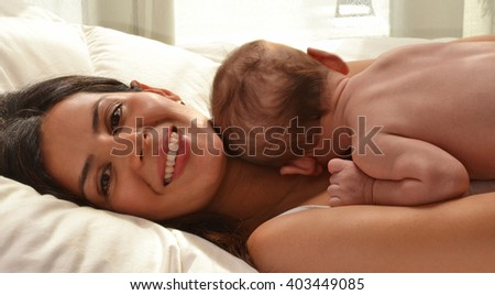 Happy mother lying down on bed with her baby. - stock photo