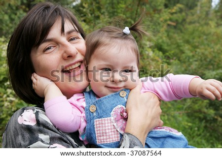 Happy mother playing with baby daughter outdoors