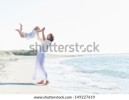 Happy mother playing with baby on beach - stock photo