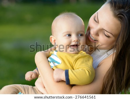 Happy mother playing with her baby in her arms - stock photo
