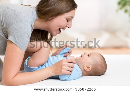 Happy mother playing with her daughter adorable baby - stock photo